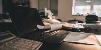 kancelari s pocitacom a kalkulackou na stole a papiermi