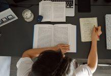 zena sedi za pracovnym stolom s mnozstvom papierov