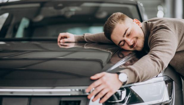 young-handsome-man-hugging-car-car-showroom_1303-20419 Kúpiť radšej nové alebo ojazdené auto?