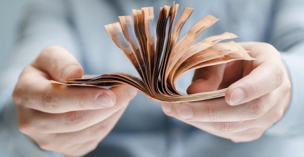 front-view-person-holding-money-1024x529 Pôžička bez dokladovania príjmov nie je mýtus